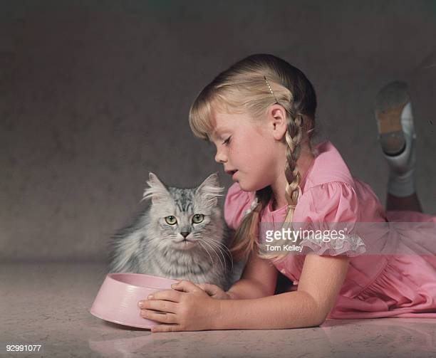 A little girl in pink dress lies down next to her cat while looking into an empty cat food bowl ca1960s