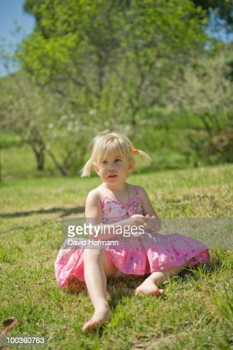 Little Girl In Pink Dress Sitting In Grass High-Res Stock -7867