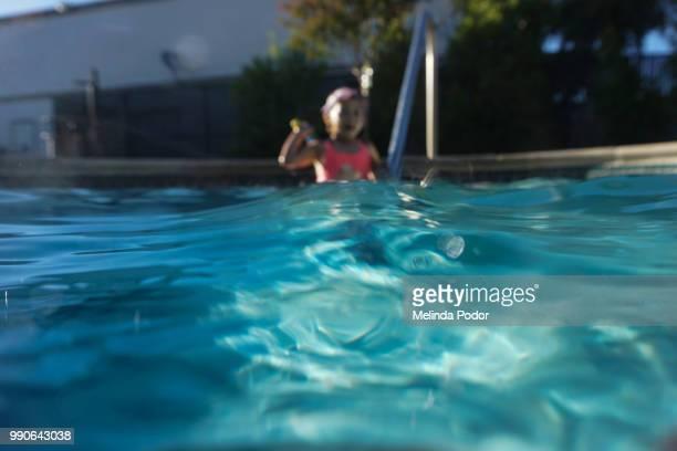 little girl in pool - focus on foreground - piscina pubblica all'aperto foto e immagini stock