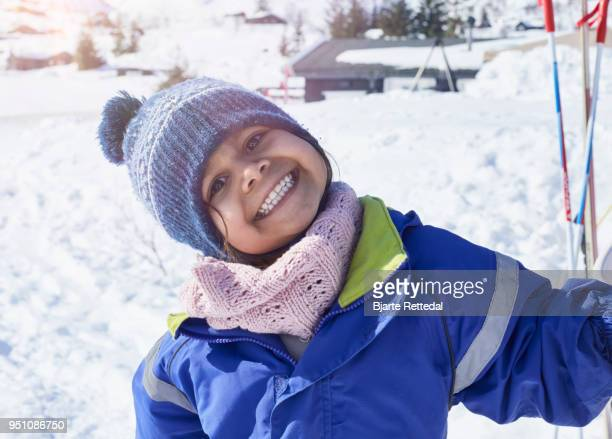 Little girl in ski outfit smiling to camera