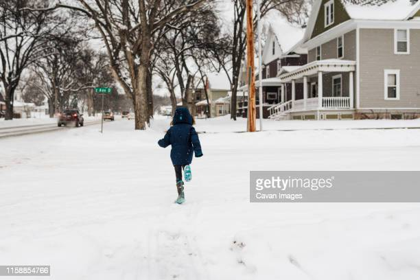 little girl in snow coat and snow boots runs across street in snow - bismarck north dakota stock-fotos und bilder