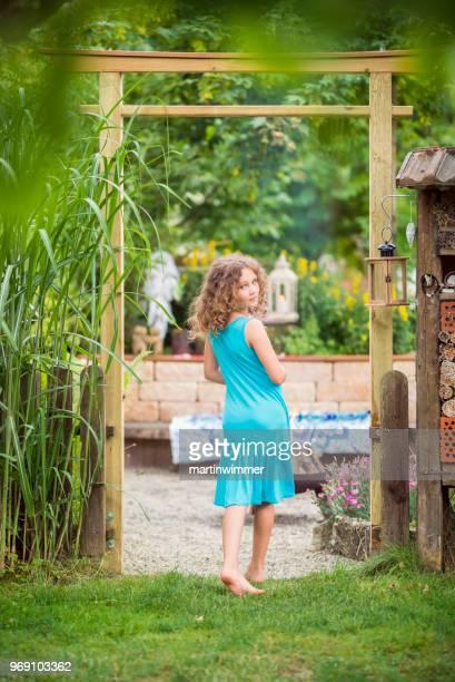 kleines Mädchen im Garten unter einem japanischen Tor