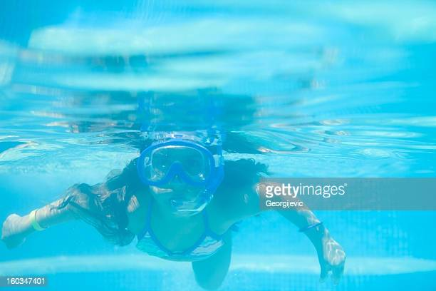 Little girl in the pool swimming underwater