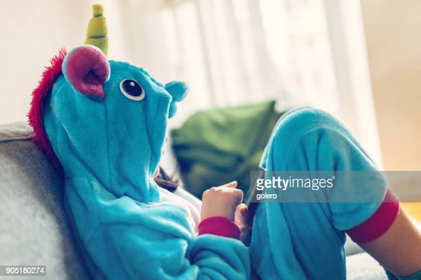 little girl in unicorn costume relaxing with mobile on couch - unicorn stock pictures, royalty-free photos & images