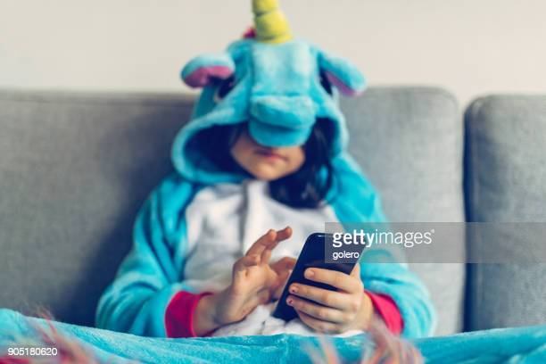 little girl in unicorn costume tapping on mobile