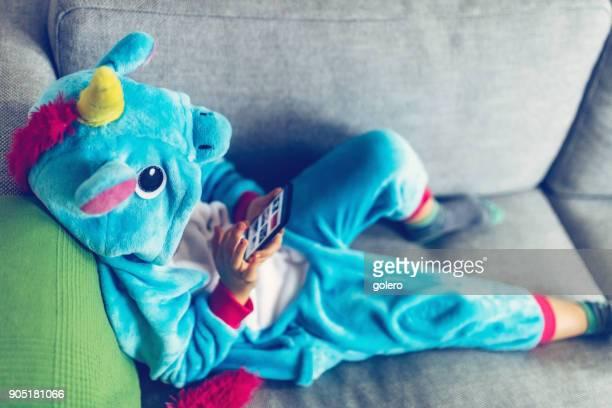kleines Mädchen mit Einhorn Kostüm auf dem Handy ansehen