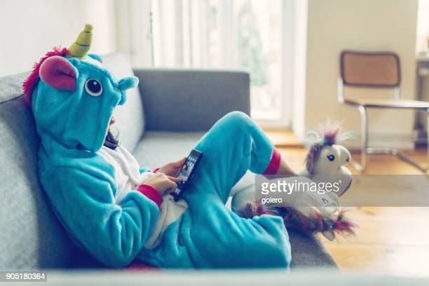 little girl in unicorn costume with mobile on couch - criança imagens e fotografias de stock