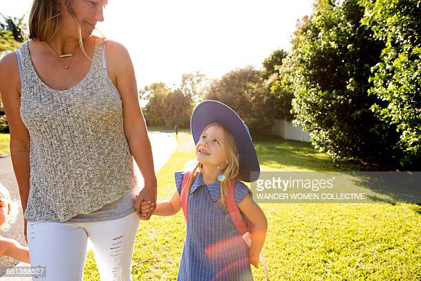 Little girl in uniform walking to school with mum