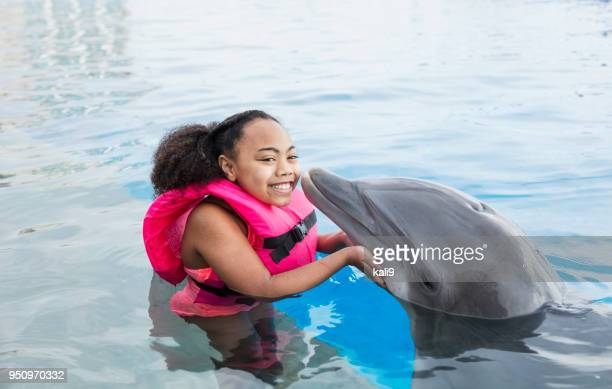 Little girl in water with dolphin getting a kiss