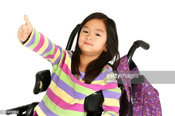 Little girl in wheelchair giving thumb's up
