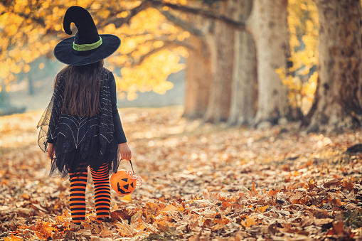 Little girl in witch costume having fun on Halloween trick or treat 1176635631