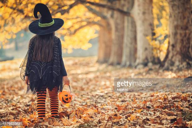 little girl in witch costume having fun on halloween trick or treat - fancy dress costume stock pictures, royalty-free photos & images