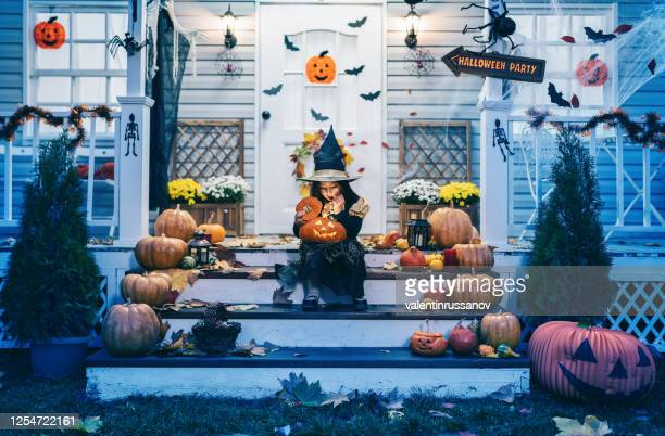little girl in witch costume sitting on the stairs in front of the house and holding jack-o-lantern pumpkins on halloween trick or treat - halloween decoration stock pictures, royalty-free photos & images
