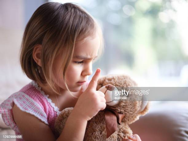 little girl is angry with her toy bear at home nearby window, child psychology concept - penalty stock pictures, royalty-free photos & images