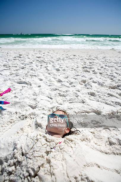 a little girl is buried in the sand up to her head at the beach with the ocean in the background. - destin beach stock pictures, royalty-free photos & images