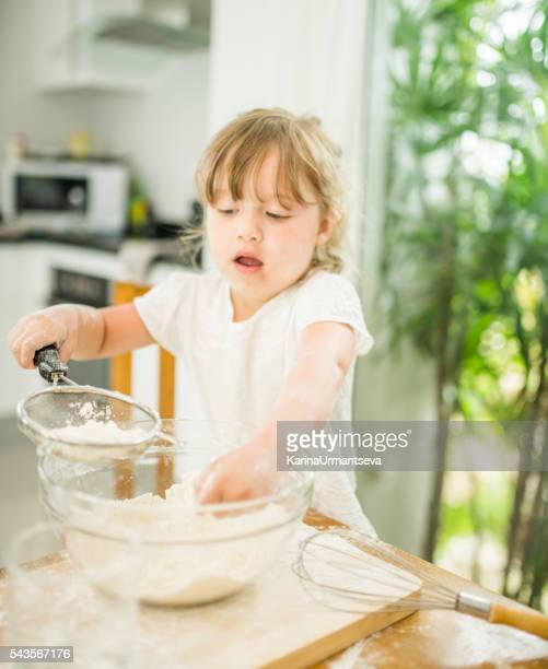 Little girl is cooking in the kitchen