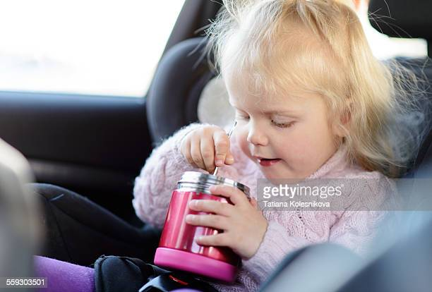 Little girl is eating lunch in the car