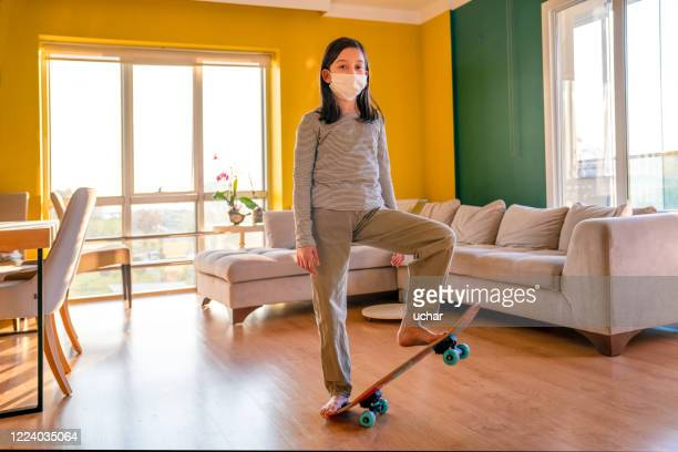 little girl is flying with skateboard inside the room - aviation hat stock pictures, royalty-free photos & images