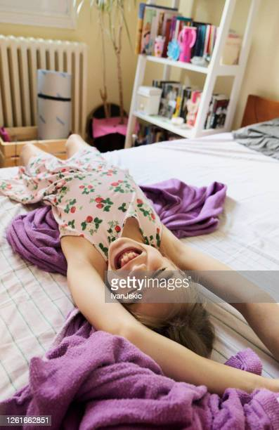 little girl is having fun stretching alone in bed - ivanjekic stock pictures, royalty-free photos & images
