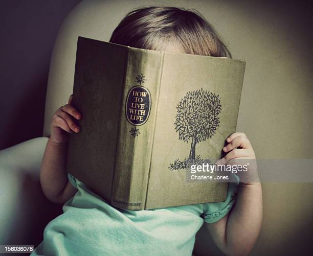 A little girl is holding a book over her face The book cover has a tree on it and the title says 'How to Live with Life'