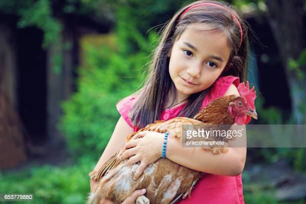 Petite fille est étreindre une poule à la ferme