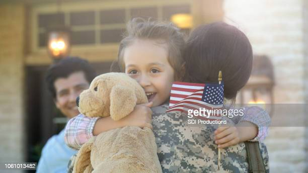 little girl is lifted into hug by a young adult female in uniform - army soldier stock pictures, royalty-free photos & images