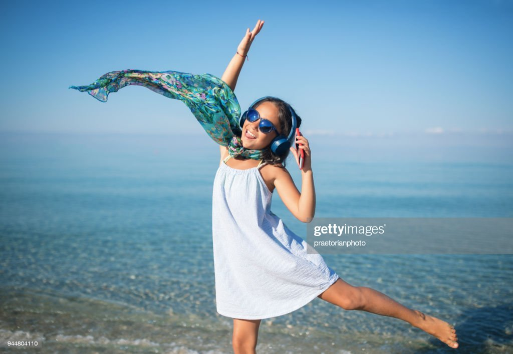 Little girl is listening the music and dancing on the beach : Stock Photo