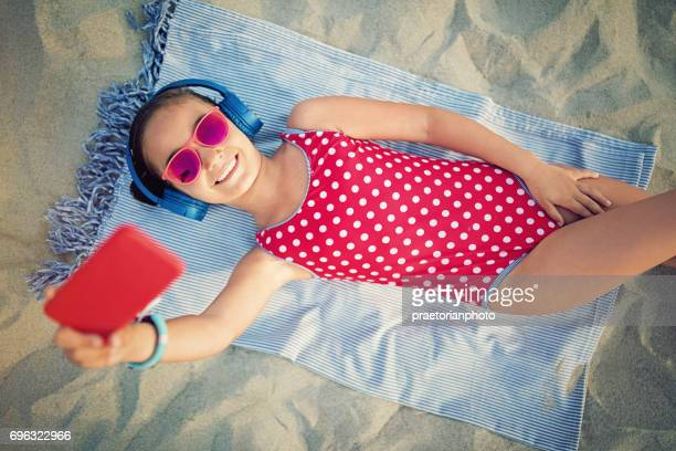 little girl is listening the music and taking selfie on the beach - little girl laying on the beach stock photos and pictures