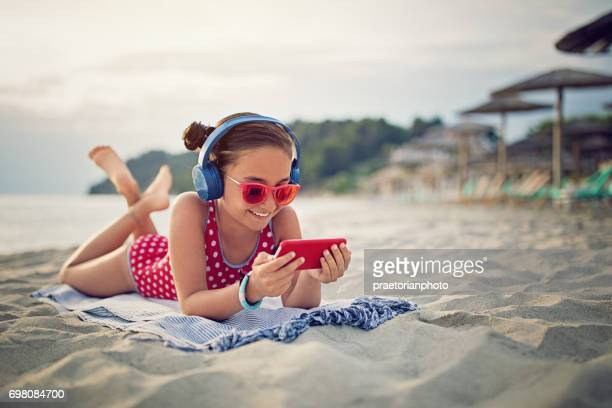 Little girl is listening the music on the beach