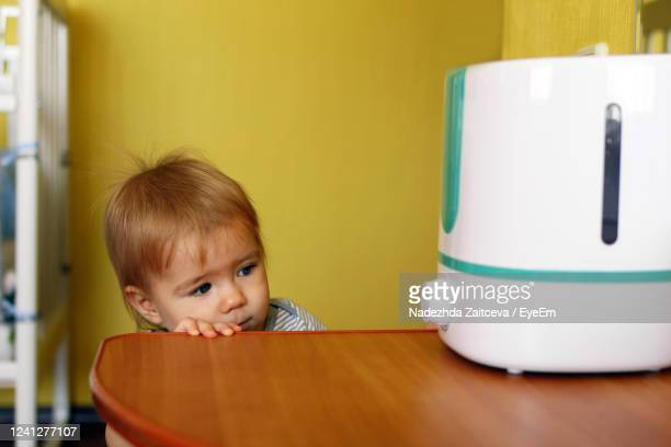 little girl is looking on a humidifier in bedroom. - humidifier stock pictures, royalty-free photos & images