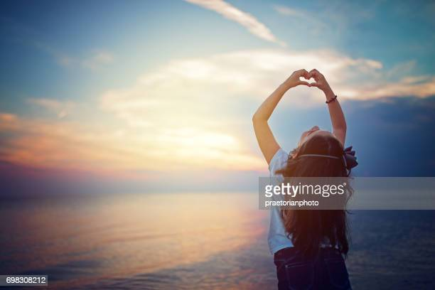 Little girl is making heart with her fingers at the front of beautiful sunset