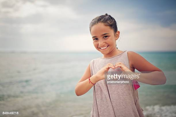 Little girl is making heart with her fingers on the beach