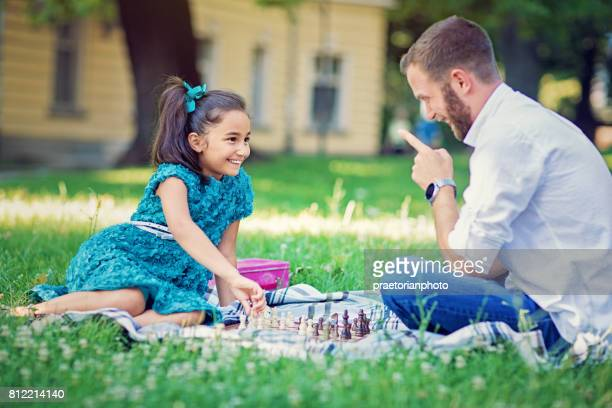 Little girl is playing chess with her father and trying to cheat