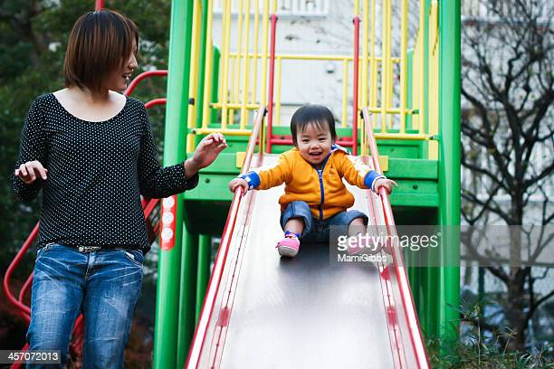 Little girl is playing slide with her mother