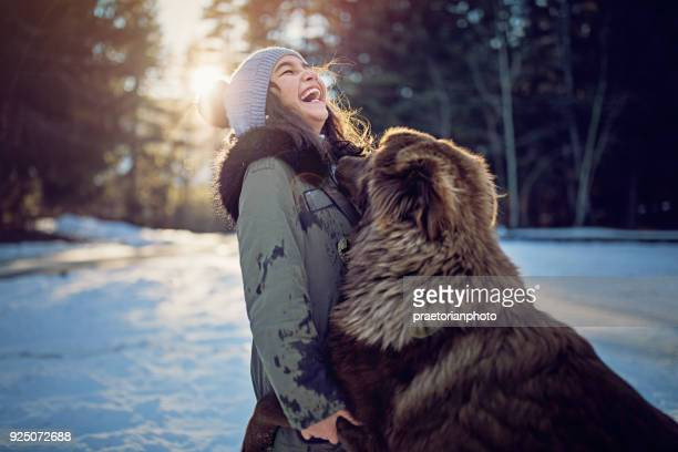 Little girl is playing with her dog in the snowy forest