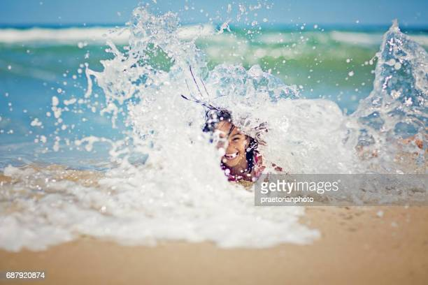 Little girl is playing with the waves on the beach