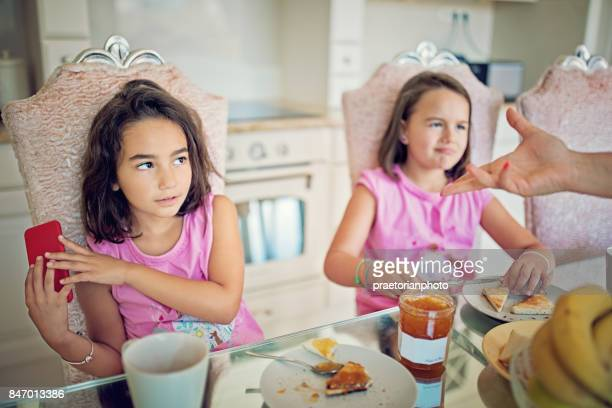 Little girl is refusing to give mobile phone to her mother at the breakfast