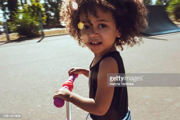 a little  girl is riding a scooter. - petites filles photos et images de collection