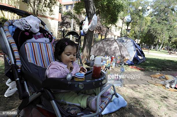 A little girl is seen ready to eat as her family camps in a park in Santiago on February 28 the day after a huge 88magnitude earthquake rocked Chile...