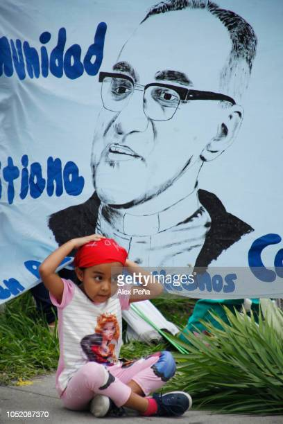 A little girl is seen sit by a placard with the image of Monsignor Oscar Arnulfo Romero on October 13 2018 in San Salvador El Salvador Romero was...