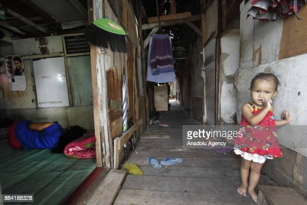 A little girl is seen standing in front of her wooden house at Kapuk Teko village Cengkareng regency of West Jakarta Indonesia on December 1 2017 The...