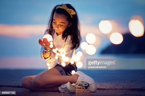 Little girl is sitting on the pier and playing with the mysterious lights