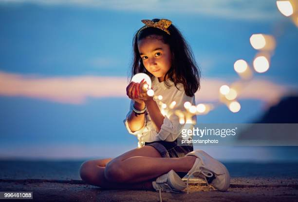 little girl is sitting on the pier and playing with the mysterious lights - firefly stock pictures, royalty-free photos & images