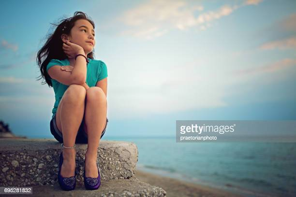 Little girl is sitting on the steps on the beach and looking the sunset over the ocean