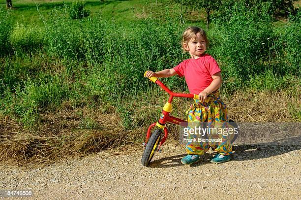 A little girl is standing beside her training bike
