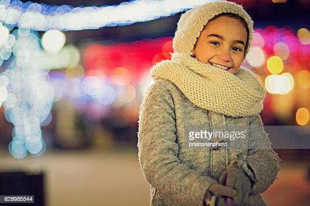 Little girl is standing on the Xmas street