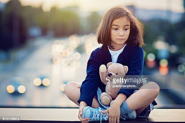 Little girl is standing sad on the bridge