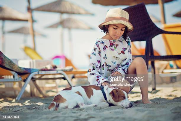 Little girl is stroking her sleeping dog under a beach umbrella
