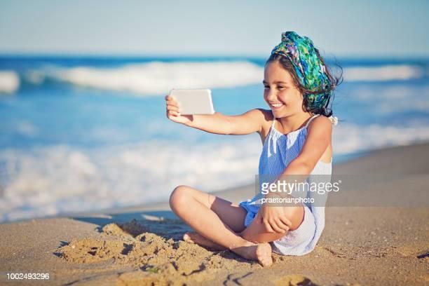 Kleines Mädchen nimmt Selfie/Making Videoanruf am Strand