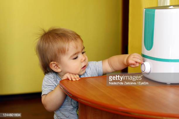 little girl is trying to turn on a humidifier in bedroom. - humidifier stock pictures, royalty-free photos & images